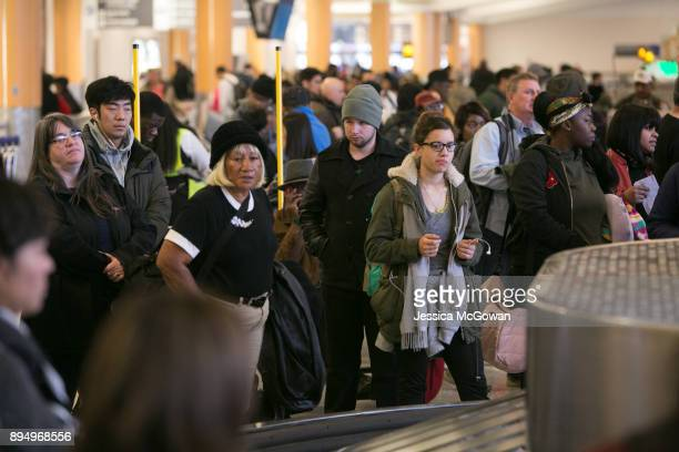 Passengers wait for baggage to arrive on the carousel in baggage claim at HartsfieldJackson Atlanta International Airport on December 18 2017 in...