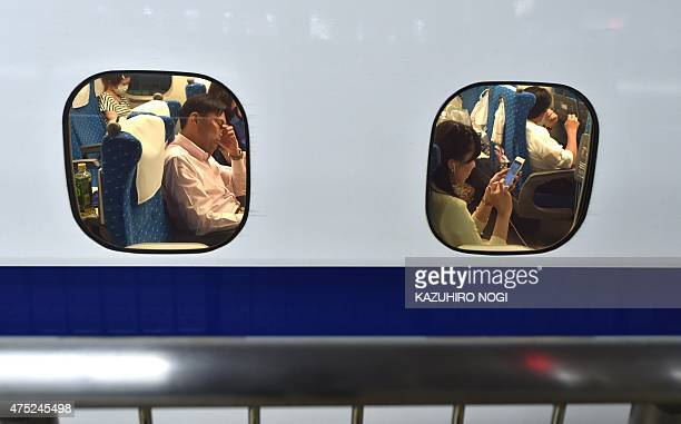 Passengers wait for 'Shinkansen' bullet train operations to resume at a train station in Tokyo following an earthquake on May 30 2015 A 78magnitude...