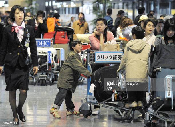 Passengers wait for the reopening of Narita International Airport early on March 24 2009 in Narita Chiba prefecture east of Tokyo a day after a FedEx...
