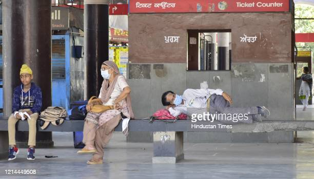Passengers wait for their bus at a bus stand during the nationwide lockdown on May 21, 2020 in Amritsar, India.