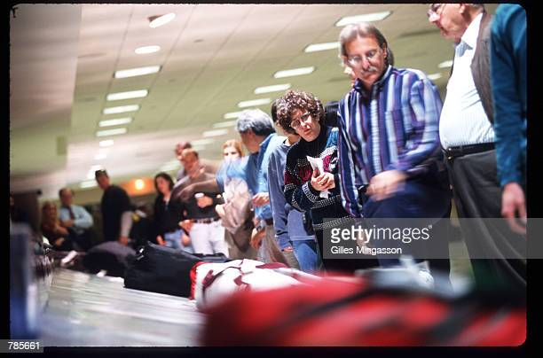 Passengers wait for their luggage at the conveyor belt at Los Angeles International Airport December 15 1997 in Los Angeles CA A primary goal of the...