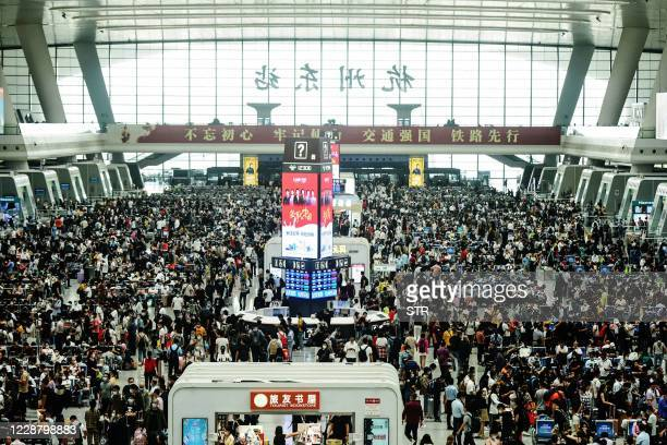 Passengers wait for their trains one day ahead of an eight-day national holiday marking China's National Day and the Mid-Autumn Festival at Hangzhou...