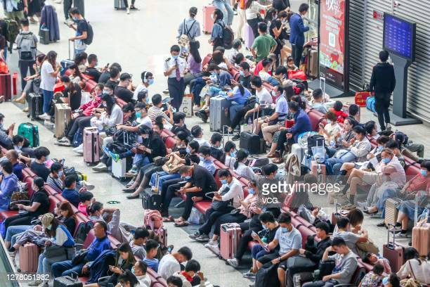 Passengers wait for trains at Zhengzhou East Railway Station on the first day of the National Day and Mid-Autumn Festival holiday on October 1, 2020...