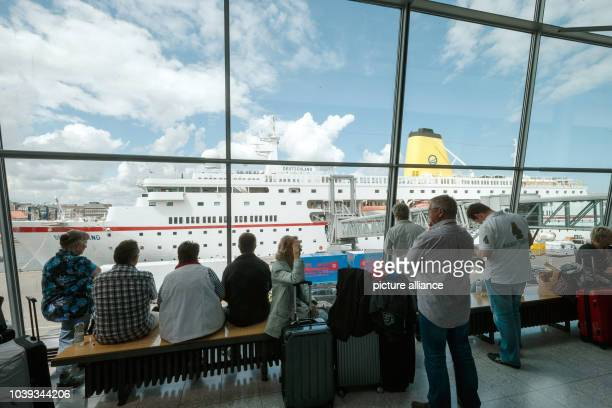 Passengers wait in a cruise terminal to check into the 'MS Deutschland' in Kiel Germany 09 June 2015 The ship made famous by the television series...