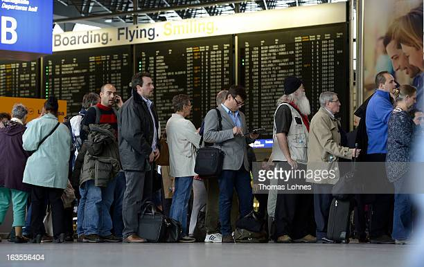 Passengers wait in a long line to rebook their cancelled flights at Frankfurt International Airport on March 12 2013 in Frankfurt am Main Germany...