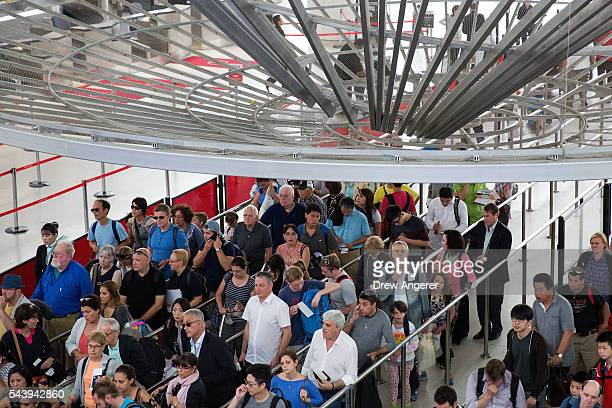 Passengers wait in a security line at John F Kennedy International Airport June 30 2016 in the Queens borough of New York City Following Tuesday's...