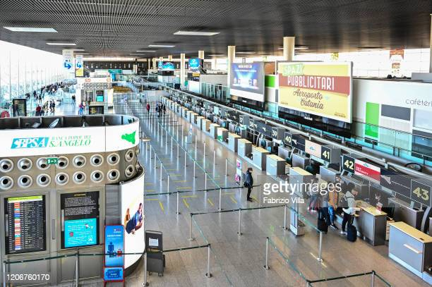 Passengers wait in almost empty queuing areas for the checkin desks at Catania airport on March 12 2020 in Catania Italy The Italian government has...