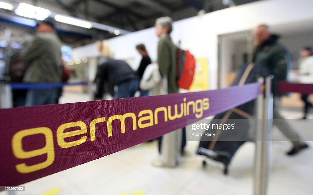 Passengers Wait In Front Of A Germanwings Check In Counter At