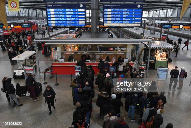 Passengers wait in front of a service counter of German railway operator Deutsche Bahn at the central station in Munich southern Germany during a...