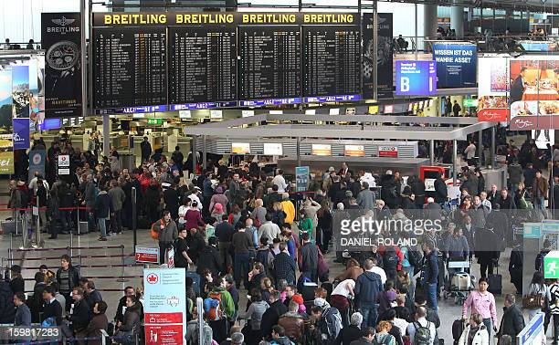 Passengers wait in front of the departure board at the Frankfurt am Main airport's main hall on January 21 2013 as more than 200 flights were...