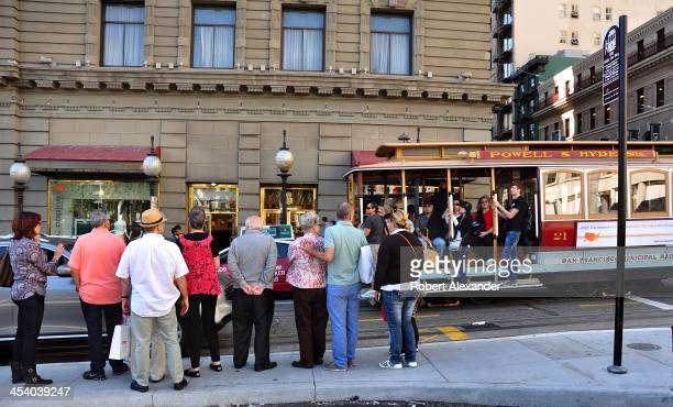Passengers wait in line for a cable car on Powell Street in San Francisco's Union Square shopping district