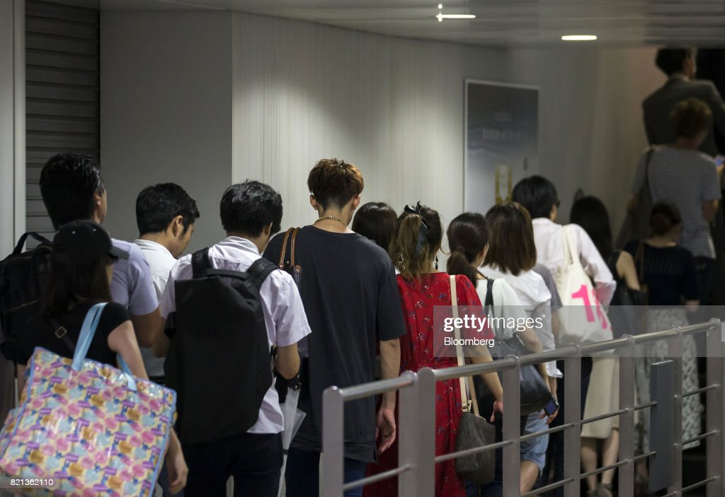 Passengers wait in line for an escalator at Shibuya Station in Tokyo, Japan, on Tuesday, July 18, 2017. July 24 marks the first dry run of a 'Telework Day' encouraging people to work from home as the city gears up to host the 2020 Summer Olympics. Authorities are seeking ways to make room for 920,000 spectatorsexpected to visit Tokyo each day during the games. Photographer: Tomohiro Ohsumi/Bloomberg via Getty Images