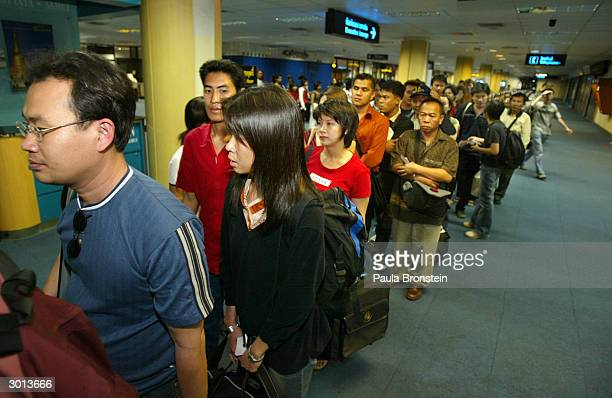 Passengers wait in line to board the Air Asia Boeing 737300 flight from Phuket to Bangkok on February 25 2004 in Phuket Thailand The airline is the...