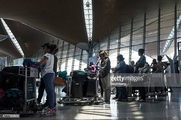 Passengers wait in line to check in for a flight at Kuala Lumpur International Airport in Sepang Malaysia on Tuesday March 11 2014 The probe into the...