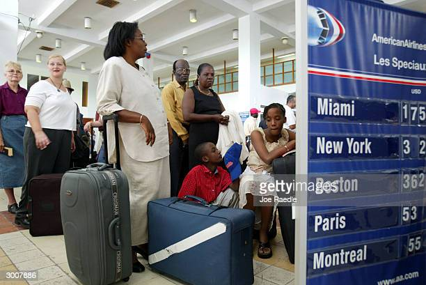 Passengers wait in line to get their American Airlines boarding pass as they prepare to leave February 23 2004 in PortauPrince Haiti 50 US Marines...