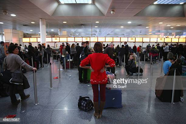 Passengers wait in the departure hall of Gatwick airport's North Terminal as severe weather has caused delays and cancellations to numerous flights...