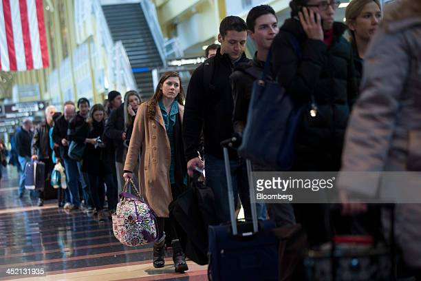 Passengers wait in the Transportation Security Administration line at Ronald Reagan National Airport in Washington DC US on Tuesday Nov 26 2013 Heavy...