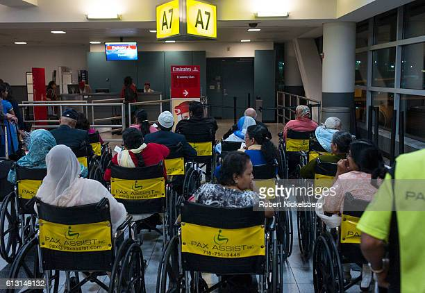 Passengers wait in wheel chairs to board an Emirates Airlines flight to Dubai August 24 2016 at the JFK International Airport in New York