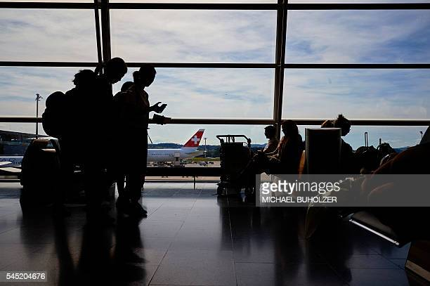 Passengers wait on July 6 2016 at the Zurich Airport in Zurich / AFP / MICHAEL BUHOLZER