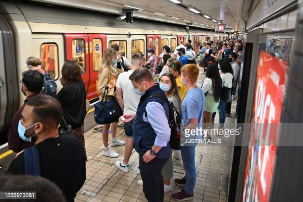 Passengers wait on the platform as they travel on the London Underground in central London on July 14, 2021. - London Mayor Sadiq Khan called for use...