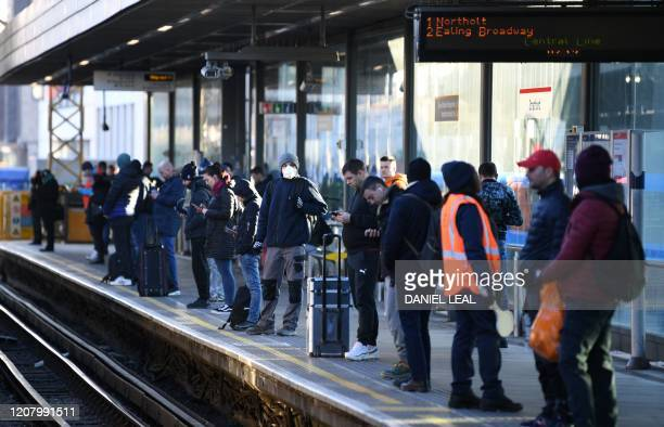 Passengers wait on the platform for a Central Line underground train at Stratford station east London March 23 2020 Amid the coronvirus pandemic...