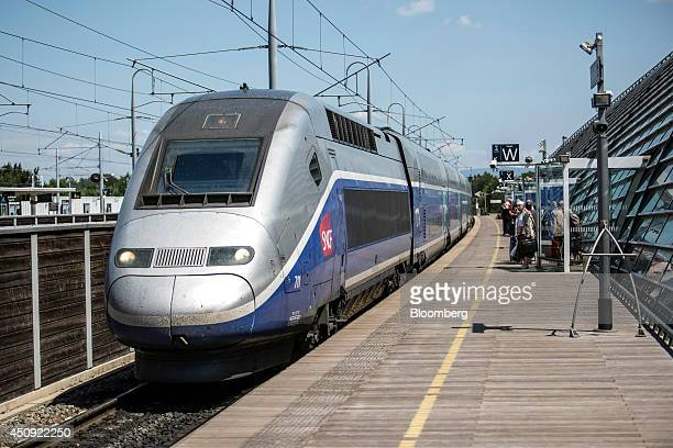 Passengers wait to board a TGV duplex highspeed train operated by Societe Nationale des Chemins de Fer and manufactured by Alstom SA as it stands in...