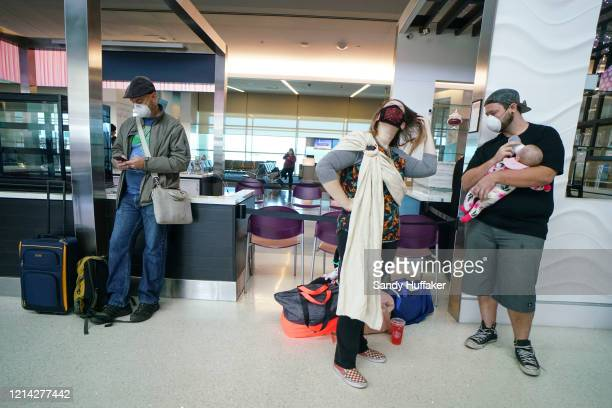 Passengers wait to board an American Airlines flight to Charlotte North Carolina at San Diego International Airport on May 20 2020 in San Diego...