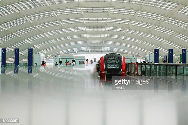 Passengers wait to board the new Airport Express train at the station in Beijing Capital International Airport on July 19, 2008 in Beijing, China....