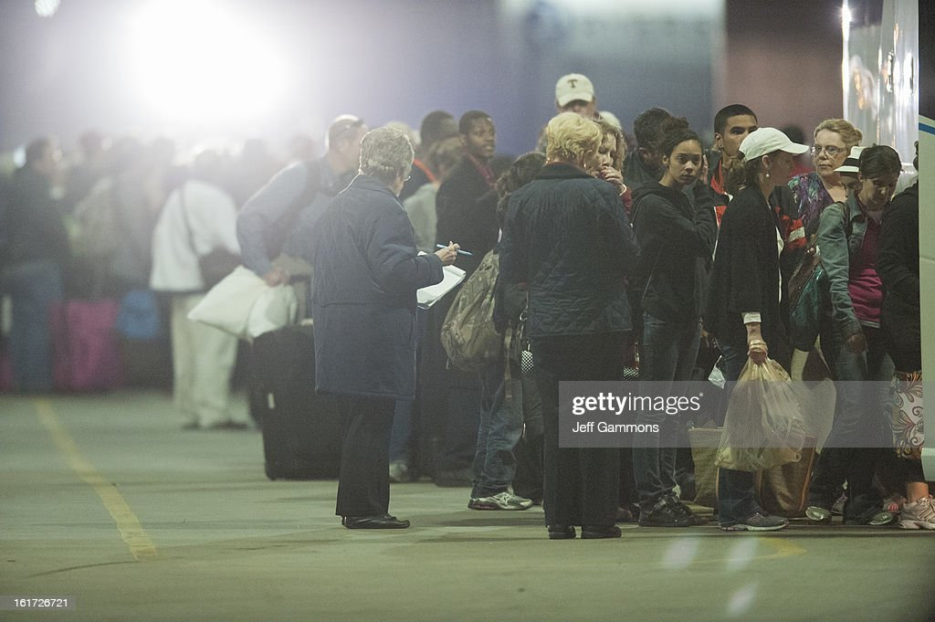 Passengers wait to leave by bus from the crippled cruise liner Carnival Triumph February 14, 2013 in Mobile, Alabama. An engine fire on February 10 left the ship and its 4,000 passengers without power and with scarce food, according to passengers onboard. While passengers reported toilets that wouldn't work, the ship was restocked with food during the days it was being towed through the Gulf of Mexico. According to reports, a few dozen people awaited the ship's arrival in Mobile, covered live by cable news network CNN.