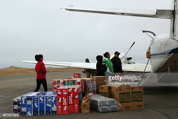 BAY AK MAY Passengers wait to load an Era Aviation airplane bound for Bethel AK in Hooper Bay AK in Hooper Bay AK on May 15 2014 Flatscreen TVs soda...