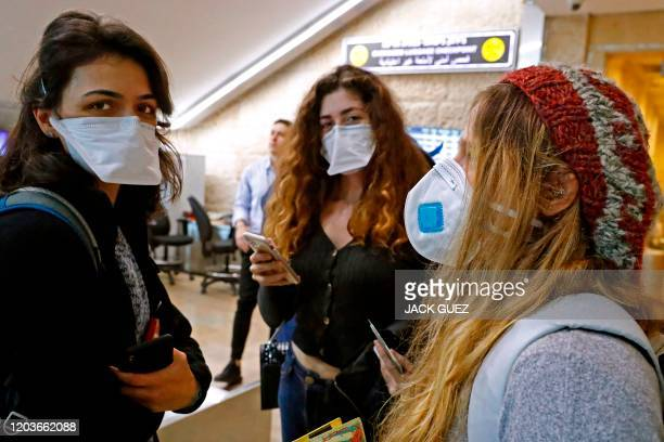 Passengers wait while wearing protective masks at Ben Gurion International Airport, near Tel Aviv, on February 27, 2020. - Israel has recorded three...