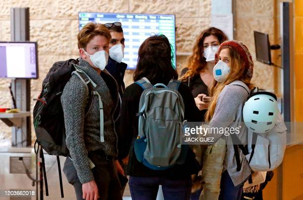 Passengers wait while wearing protective masks at the arrival hall of Ben Gurion International Airport, near Tel Aviv, on February 27, 2020. - Israel...