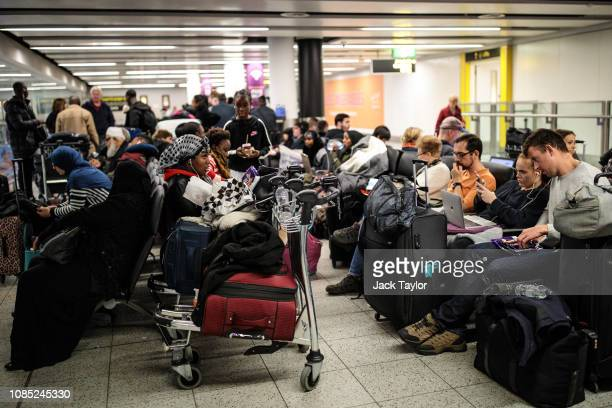 Passengers wait with their luggage in the South Terminal building at London Gatwick Airport after flights resumed today on December 21 2018 in London...