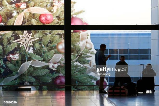 Passengers wait with their luggage near a festive display in the main entrance of the north terminal at Gatwick airport in Crawley UK on Friday Dec...