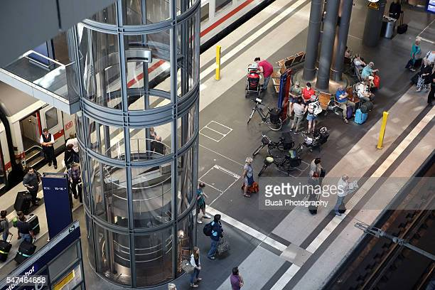 Passengers waiting alongside railway tracks inside Berlin Central Station (Hauptbahnhof), the main station of Berlin, Germany