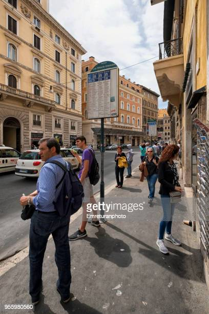 passengers waiting at a bus stop in a rome street on a sunny day. - emreturanphoto stock pictures, royalty-free photos & images