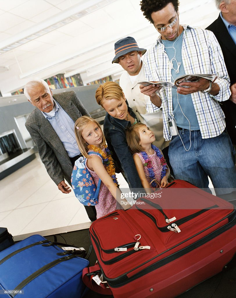 Passengers Waiting at an Airport Baggage Collection Conveyor Belt : Stock Photo