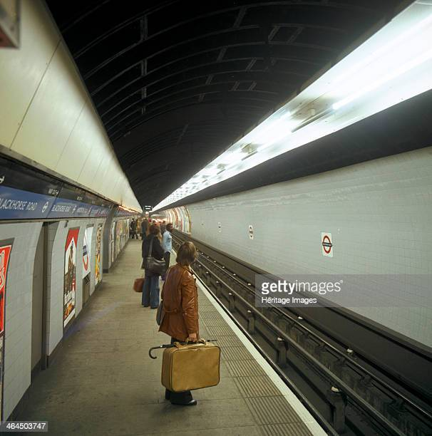 Passengers waiting at Blackhorse tube station on the Victoria Line London 1974 A traveller in a typical mid 1970s leather Jacket carries a plastic...