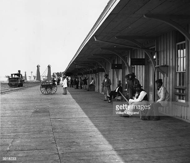 Passengers waiting at the Clifton Depot on the Great Western Railway Canada The Niagara Suspension Bridge is seen in the background