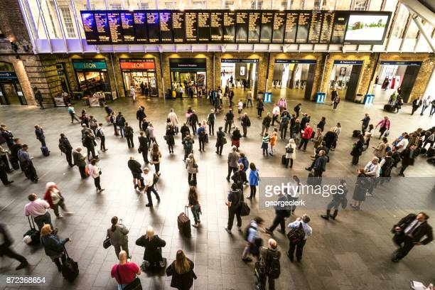 Passengers waiting for platform information at King's Cross station in London