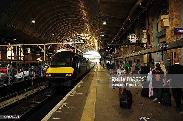 CONTENT] Passengers waiting the train towards Edinburg on a train platform located in King Cross train station London England UK The train is on the...