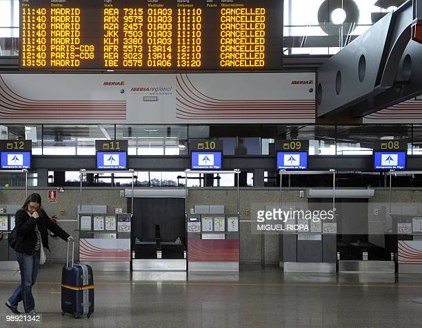 A passengers waits near a checkin under a departure board after flights were cancelled from the Peinador airport in Vigo northwestern Spain on May 8...