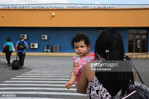 Passengers walk across the tarmac at Jose Marti International Airport after arriving on a charter plane operated by American Airlines January 19,...