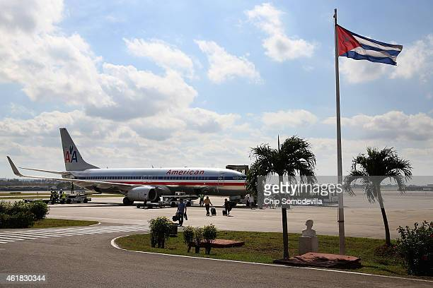 Passengers walk across the tarmac at Jose Marti International Airport after arriving on a charter plane operated by American Airlines January 19 2015...