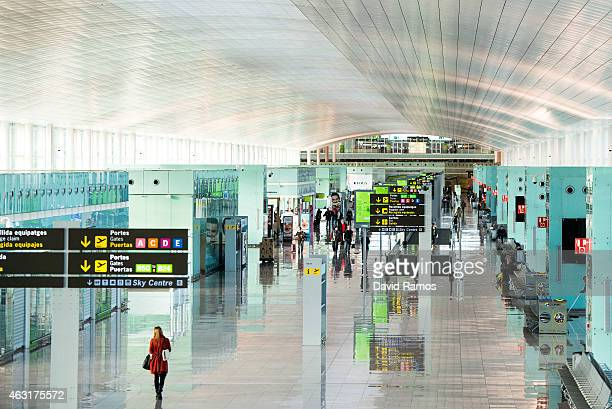 Passengers walk along the departures hall at Aena operated Barcelona El Prat International Airport on February 11 2015 in Barcelona Spain Shares in...
