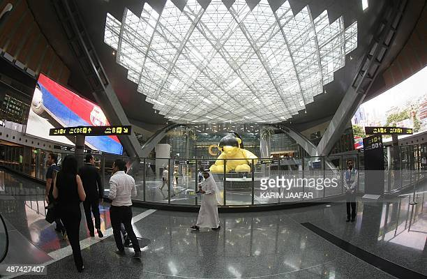 Passengers walk at a terminal upon their arrival at the new Hamad International Airport on April 30 2014 in Doha The first commercial flight...