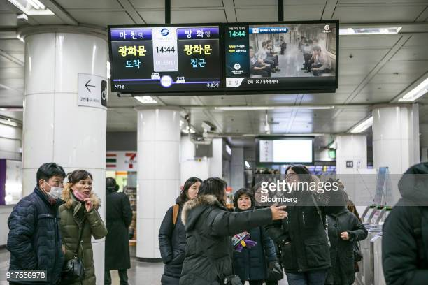 Passengers walk below a monitor displaying the estimated arrival times of subway trains inside a subway station in Seoul South Korea on Sunday Jan 28...