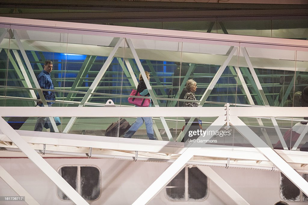 Passengers walk down the terminal from the crippled cruise liner Carnival Triumph February 14, 2013 in Mobile, Alabama. An engine fire on February 10 left the ship and its 4,000 passengers without power and with scarce food, according to passengers onboard. While passengers reported toilets that wouldn't work, the ship was restocked with food during the days it was being towed through the Gulf of Mexico. According to reports, a few dozen people awaited the ship's arrival in Mobile, covered live by cable news network CNN.