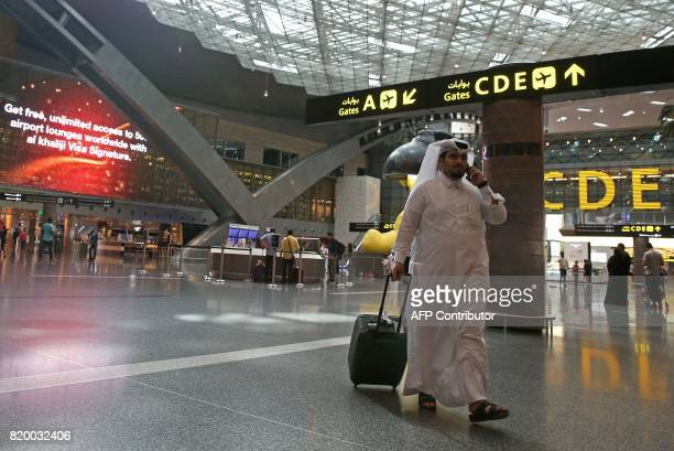 Passengers walk in the departures lounge at the Hamad International Airport in Doha on July 20 2017 / AFP PHOTO / STRINGER
