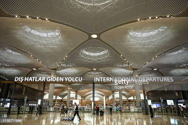Passengers walk in the international departures hall of Istanbul Airport on the first day after moving from Ataturk International airport on April 6...